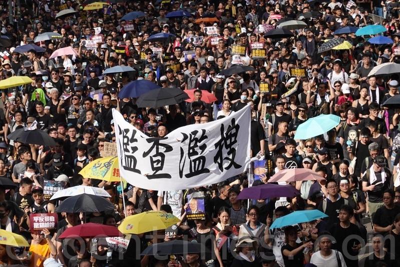 有市民舉起起橫額抗議警方「濫查濫搜」。(余鋼/大紀元)