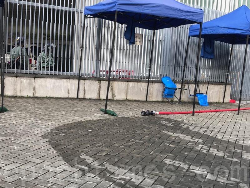 特首辦外有大支水喉,示威者一度起哄,質疑警員計劃使用水炮清場,民主黨立法會議員許智峯到場了解。(蔡雯文/大紀元)