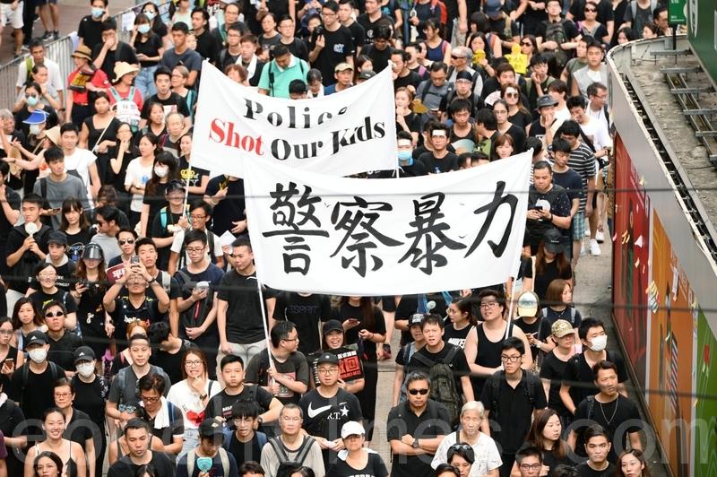有市民舉起橫額抗議警察暴力。(宋碧龍/大紀元)