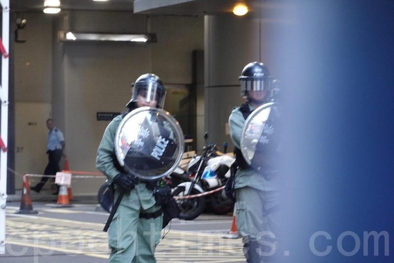 有穿上防暴裝備的警察在水馬後戒備。(余鋼/大紀元)