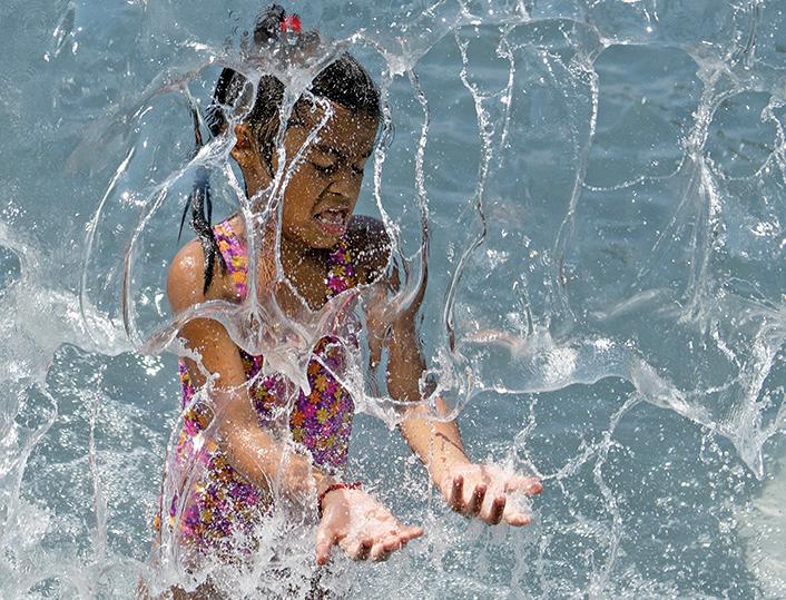 上周末,美國多地的熱浪襲擊將達到高峰。圖為華盛頓特區的一個孩子在玩水解暑。(AFP)