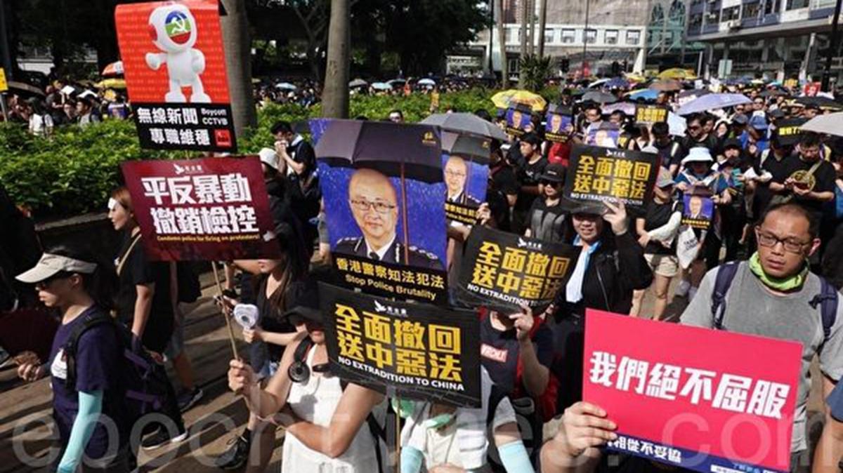 7月21日,香港民陣發起的反送中遊行隊伍中,參加遊行的市民手持各種標語和海報表達心聲。(余鋼/大紀元)