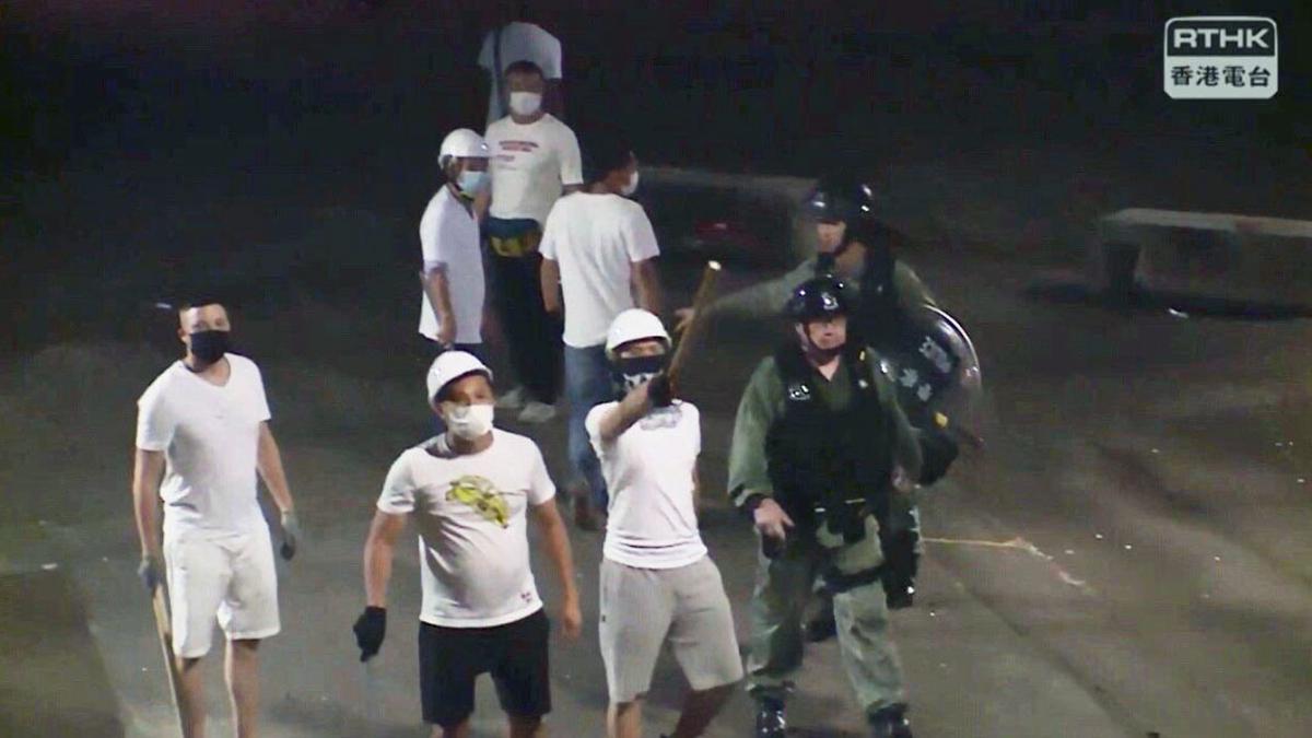 警方21日晚沒有拘捕施襲的白衣人,辯稱「未見任何人持攻擊性武器」,但現場記者拍攝的畫面,清楚可見白衣人手持長棍及鐵枝,站在防暴警察身旁。(影片截圖)