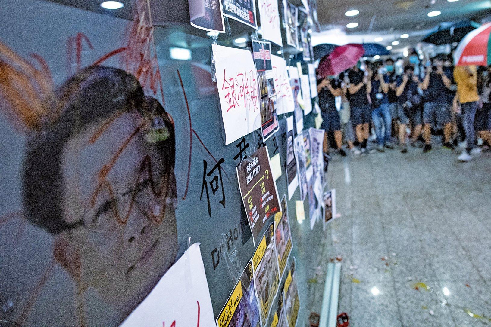 7月21日,43萬人反送中大遊行後,香港白衣暴徒在元朗攻擊示威人士、記者,多人受傷。圖為與白衣暴徒握手表支持的親共建制派議員何君堯辦公室,7月22日被憤怒的民眾貼滿標籤。(AFP)