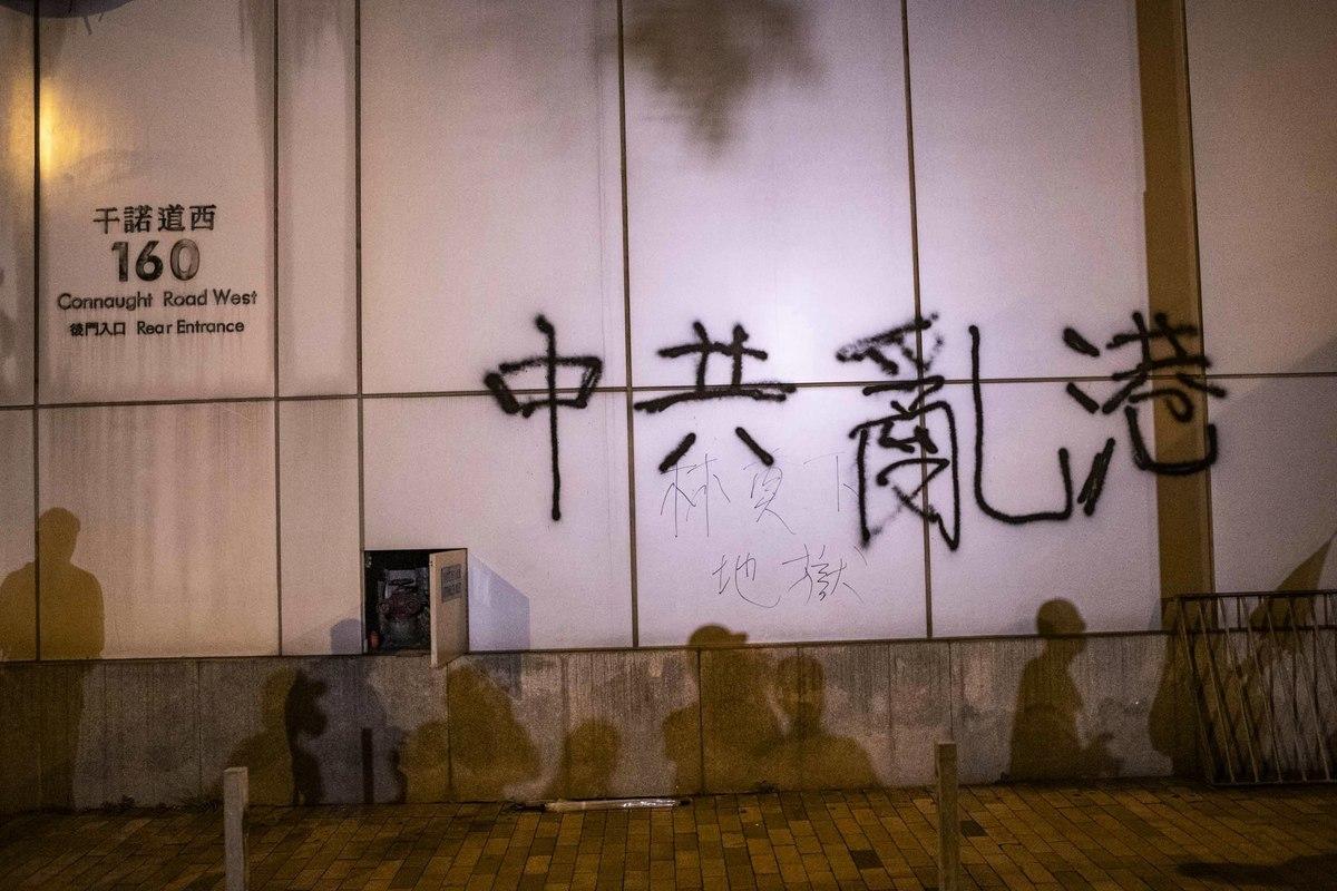 7月21日,香港民陣發起的反送中遊行,晚間有示威者聚集在中聯辦外,並在其外牆上塗鴉抗議。(余鋼/大紀元)