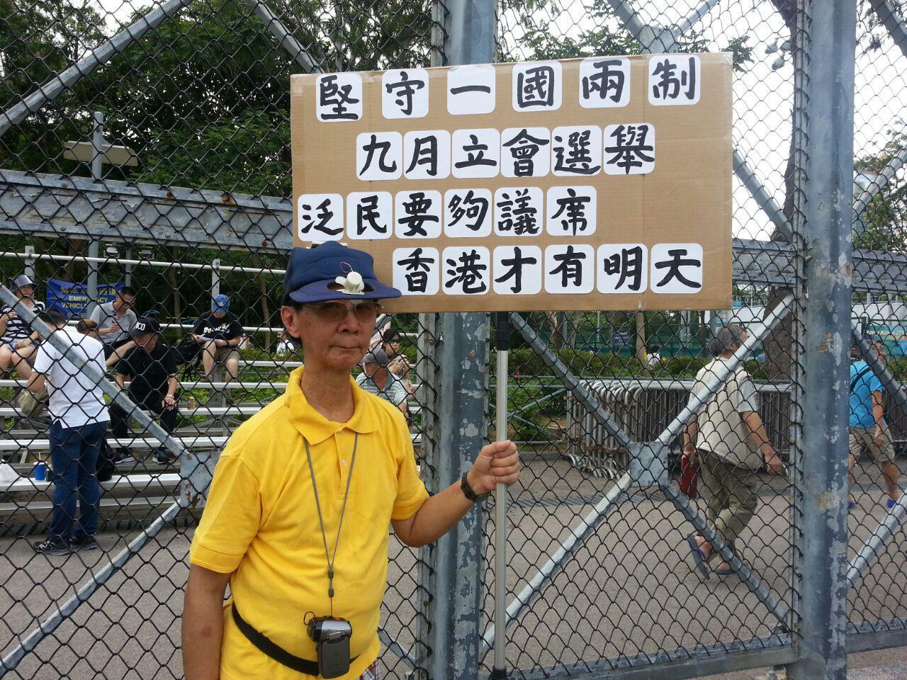 70歲市民梁先生手持自製標語牌參與遊行(大紀元)