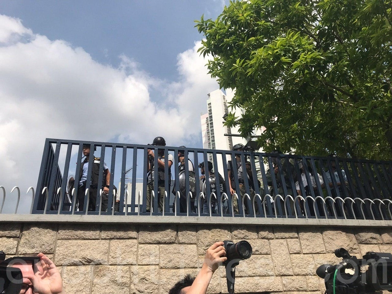 一牆之隔的警署內,警察穿上防暴裝備、手持盾牌,站在高位觀察。(林怡/大紀元)