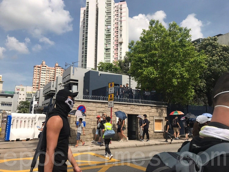 黑衣市民陸續經過元朗警署,有序地前往水邊村遊樂場。(林怡/大紀元)