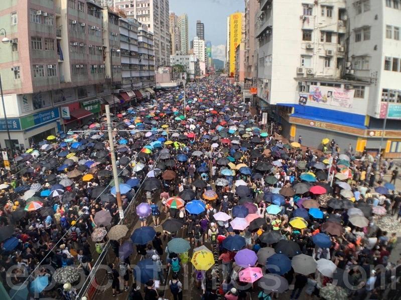 由於到元朗的市民太多,人潮佔據了青山公路元朗段(俗稱「大馬路」)、豐年路等,人群甚至走到輕鐵路軌上。(李逸/大紀元)