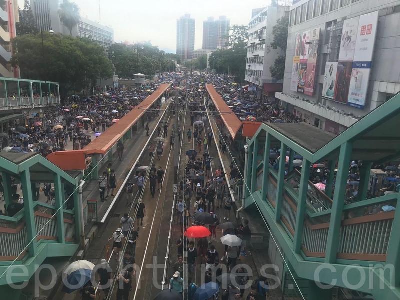 人潮佔據了豐年路等,人群甚至走到輕鐵路軌上。(蔡雯文/大紀元)