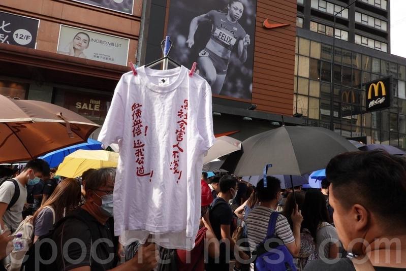 有市民舉起白衣T-shirt,上面以紅字寫上「黑社會害人不淺!血債血償!還我公道!」。(余鋼/大紀元)