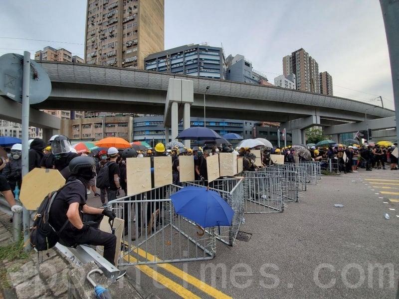 有示威者在元朗工業邨附近以鐵馬築起防線,部份人手持木板作盾牌。(余鋼/大紀元)
