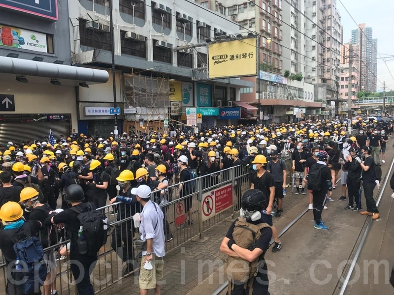 在大棠路輕鐵站附近有一批戴上頭盔的示威者留下與警方對峙。(余鋼/大紀元)