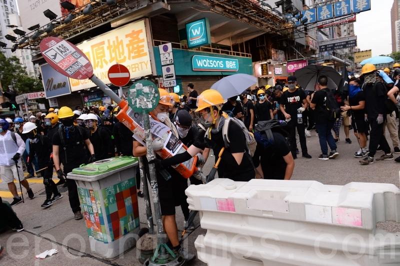 在大棠路輕鐵站附近,示威者以水馬、巴士站牌、垃圾筒等築起防線。(宋碧龍/大紀元)