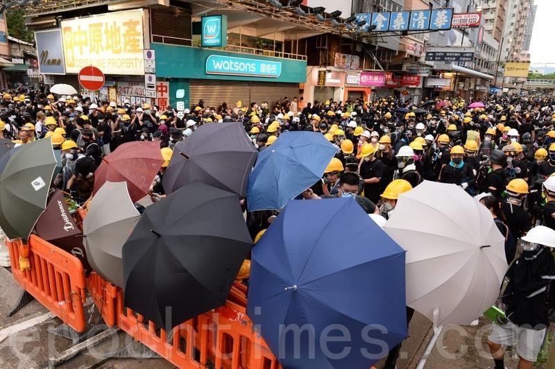 有在前線的示威者打開雨傘戒備。(宋碧龍/大紀元)