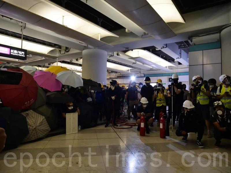 有示威者用滅火筒和消防喉,試圖阻止警方再進入西鐵站。(龐大衛/大紀元)