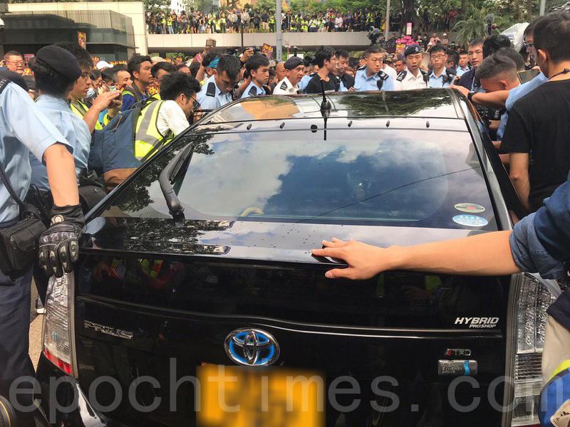 一輛黑色私家車在終審法院外被市民包圍,現場消息指市民發現車上有警員,其後私家車由警察護送離開,大量市民尾隨車輛衝出馬路。(林怡/大紀元)