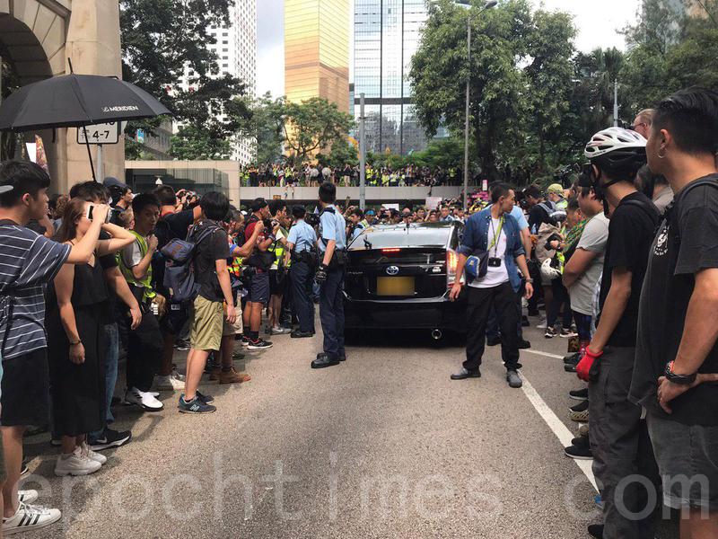 一輛黑色私家車在終審法院外被市民包圍,現場消息指市民發現車上有警員,其後私家車由警察護送離開。(林怡/大紀元)