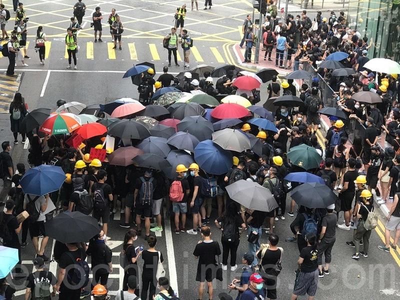在灣仔警察總部外,也有一批示威者開始聚集,他們打開雨傘圍在一起商討。(林怡/大紀元)