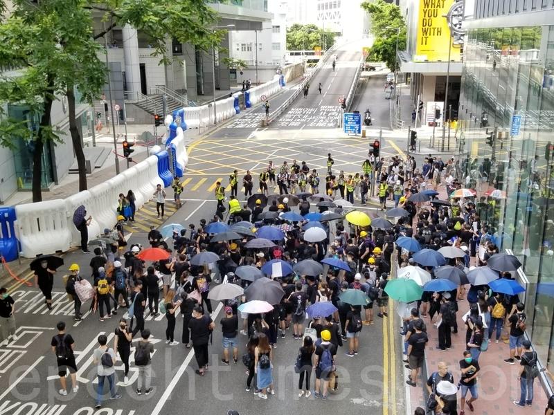 在灣仔警察總部外,也有一批示威者開始聚集,他們打開雨傘圍在一起商討。(宋碧龍/大紀元)