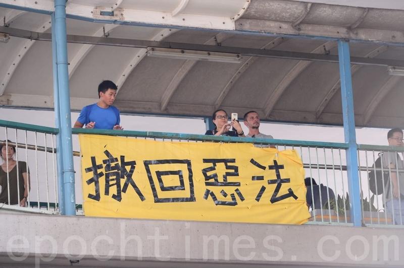 有市民在信德中心附近的天橋上掛起「撤回惡法」的橫額。(宋碧龍/大紀元)