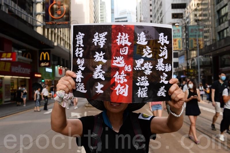 遊行隊伍經過上環西港城,有市民舉起寫有五大訴求的海報。(宋碧龍/大紀元)