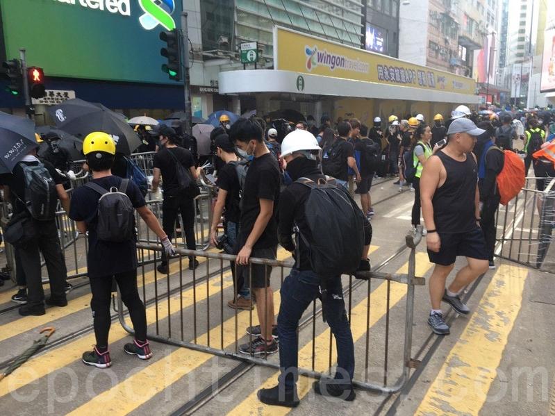 有市民在怡和街用欄杆鐵馬等築起防線。(孫青天/大紀元)