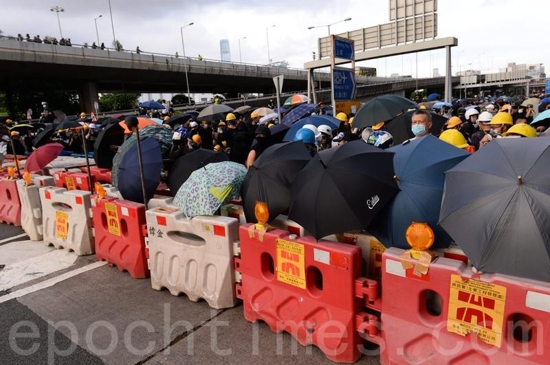 市民用水馬築起防線,又放置雨傘戒備。(宋碧龍/大紀元)