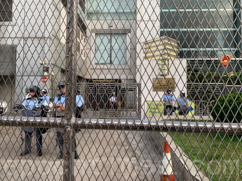 中聯辦正門則被水馬和鐵閘重重包圍,有警員把守。(李逸/大紀元)