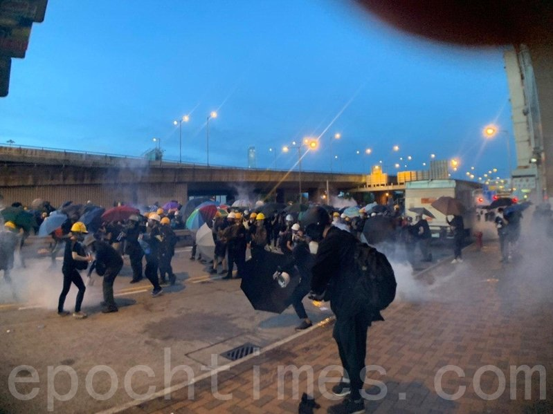中聯辦正門附近干諾道西,警方出示紅旗後,很快施放多枚催淚彈,一邊高速向前推進。(李逸/大紀元)