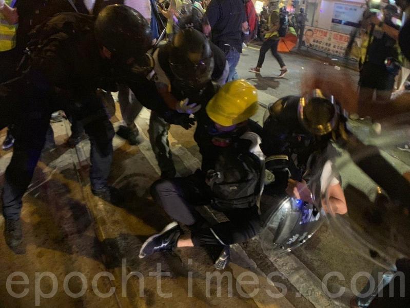警方速龍小隊也在8時突然衝前,警方並施放催淚彈,十多位示威者被制服在地,雙手被索帶索緊。(李逸/大紀元)