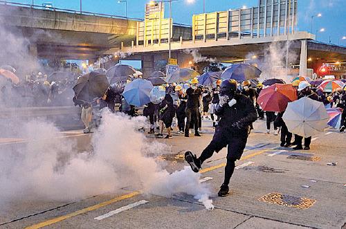示威者嘗試踢走催淚彈。(李逸/大紀元)