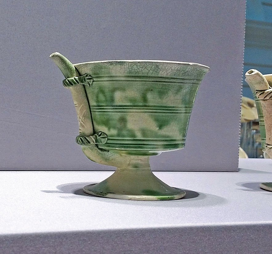 【附圖2】唐代鞏縣窯製作的白釉綠彩瓷吸杯。外面有一根吸管與杯底相連。(沈靜/大紀元)