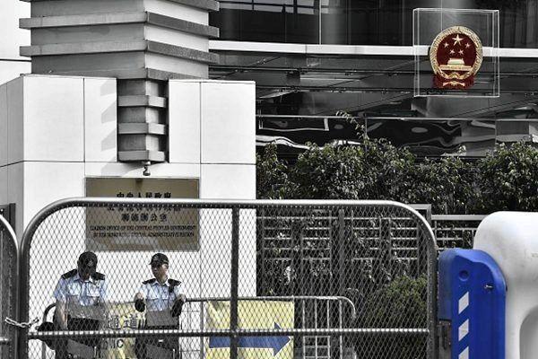 中聯辦大樓新換的中共徽章,被安上水晶棺,有多名警員巡邏。(ANTHONY WALLACE/AFP/Getty Images)