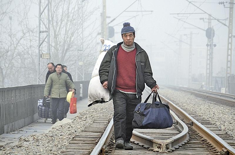 中國農民工能化解樓市的庫存嗎?答案基本上是否定的。圖為北京的農民工沿著鐵路行走。(Getty Images)