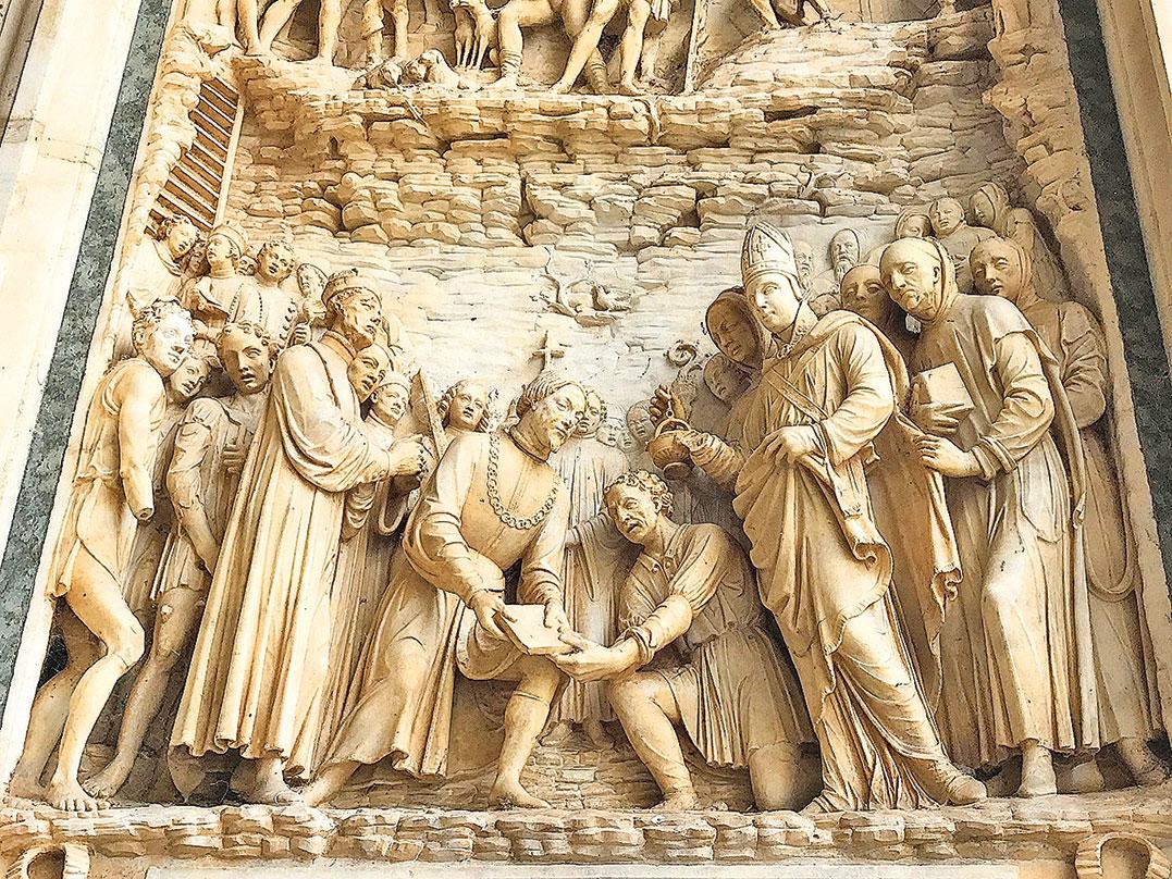 雕刻表現的是建築師手裏拿著建造修道院的第一塊磚石。(章妮妮/大紀元)