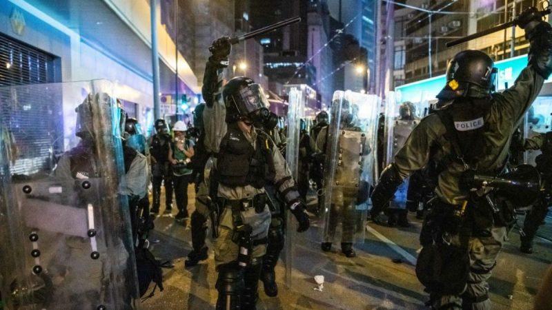 香港防暴警察於2019年7月28日在香港上環地區強行驅散示威者期間,舉起警棍向其他警員示意。(Laurel Chor/Getty Images)