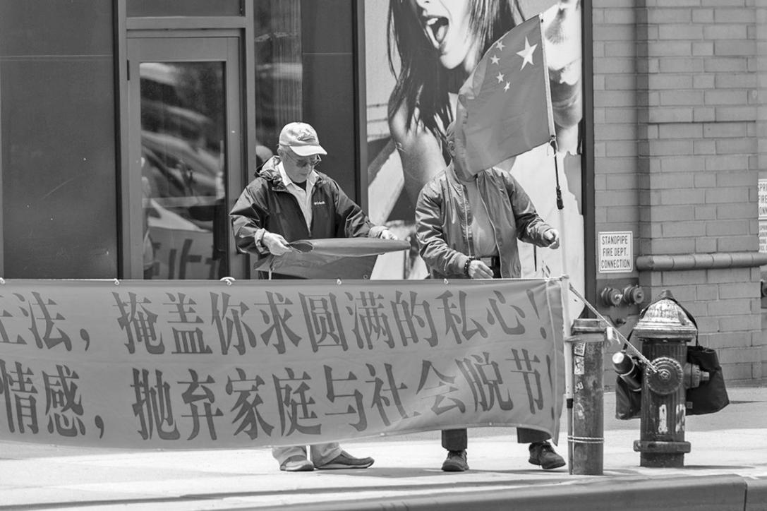 NINGXIANG LIU和 WAY H.QIU,常年在紐約中領館前在法輪功學員旁邊打出誣衊法輪功的橫幅。(明慧網)