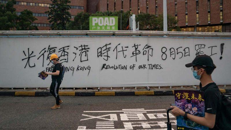 圖為8月3日,香港示威者走過一個呼籲罷工的標語。(Anthony Kwan/Getty Images)