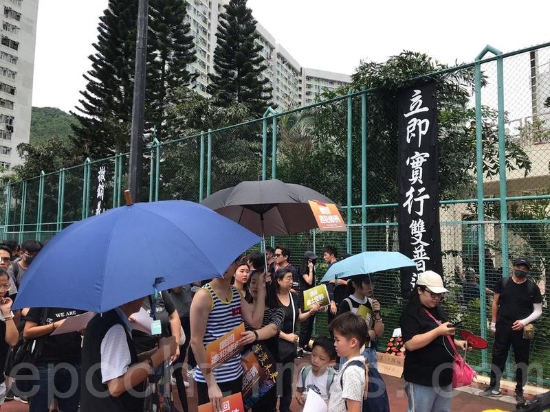 寶翠公園聚集越來越多人,大會在場內掛起寫有遊行主題的直幡。(林怡/大紀元)