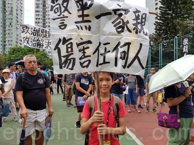 有小朋友舉起紙牌兩面分別寫有「警黑一家親 傷害任何人」及「Hong Kong Police Shame On U」。(駱亞/大紀元)