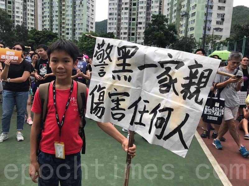 今年11歲的莊同學,曾多次參與遊行,今次再次和媽媽一起帶著自製的標語上街。(林怡/大紀元)