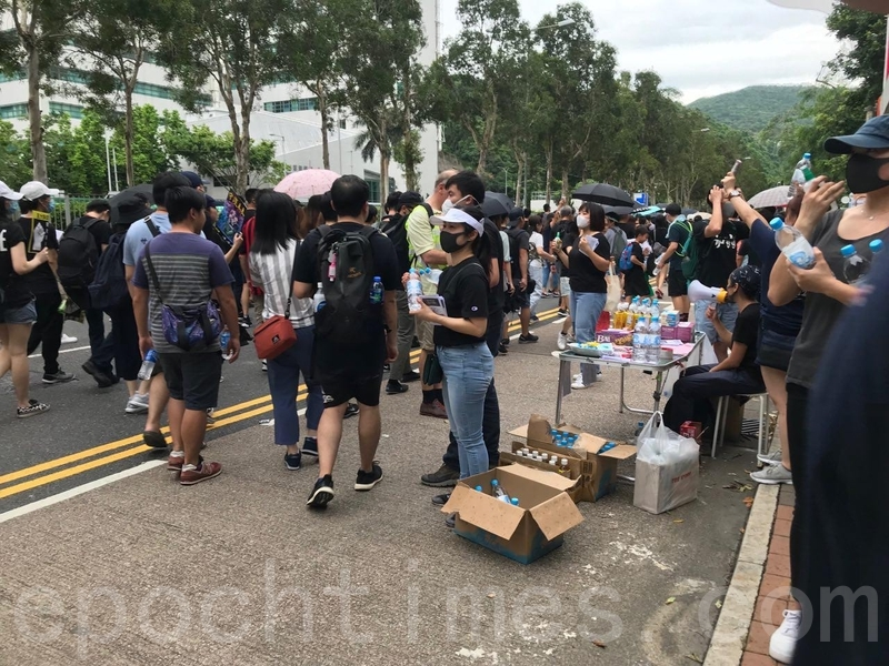 有市民在添水站向遊行市民派發樽裝水和食物。(蔡雯文/大紀元)