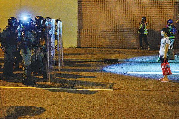 一名穿拖鞋疑似黃大仙女街坊,8月4日凌晨在黃大仙警署前,無懼地站在防暴警前。(PHILIP FONG/AFP/Getty Images)