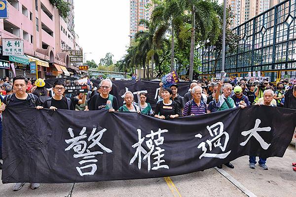 8月3日旺角再遊行,一眾銀髮族手持黑色橫額「警權過大」,帶領遊行隊伍前進。(宋碧龍/大紀元)