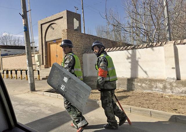 中共對新疆採取極端監控,新疆被指成為一個露天監獄。圖為2018年2月17日,新疆和田街上巡邏的警察。(Getty Images)