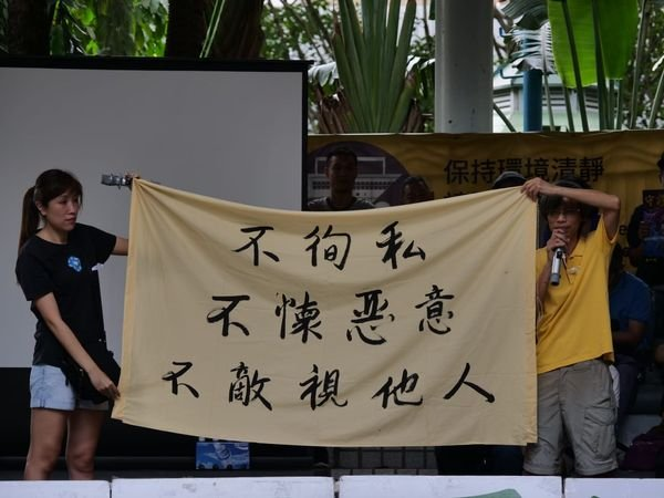 集會發起人與宣讀宣言的女士一起拉起寫有「不徇私 不懷惡意 不敵視他人」的橫幅。(龐大衛/大紀元)