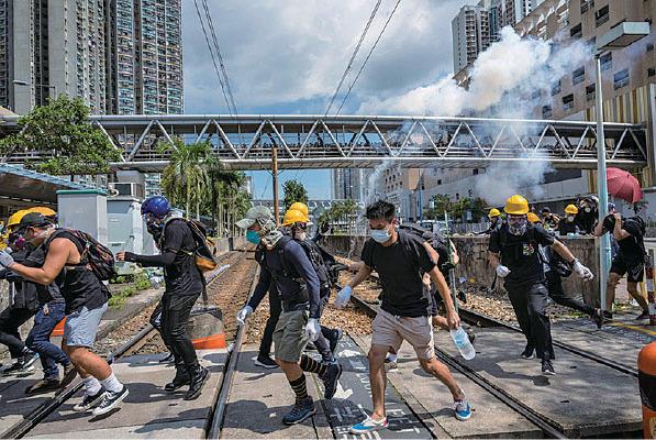 在2時半後,警方於天水圍警署外多次發射催淚彈,有示威者走避。(Billy H.C. Kwok/Getty Images)