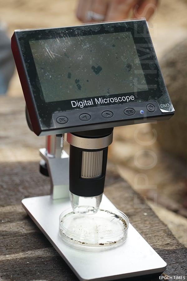 用顯微鏡觀察萃取出來的微塑膠。(曾蓮/大紀元)