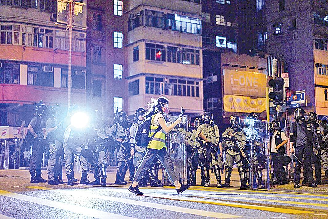 面對香港局勢不斷升級,大紀元新唐人團隊,從6月15日200萬人反送中大遊行開始,每個周末、重大活動都進行第一現場直播。圖為大紀元新唐人紐約特派記者柯婷婷(中)在直播報道中。(李明真/大紀元)